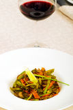 Meat dish with vegetables in a plate and a glass of red wine Stock Photos