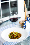 Meat dish with vegetables in a plate and a glass of red wine Stock Images