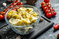 Meat dumplings in a glass bowl and cherry tomatoes. On black rustic background stock image