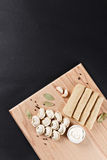 Meat dumplings and pancakes on cutting board on black paper. pel Royalty Free Stock Photography
