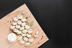 Meat dumplings and pancakes on cutting board on black paper. pel Stock Images