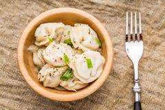 Meat dumplings - russian pelmeni, ravioli with meat on a wooden plate Stock Image