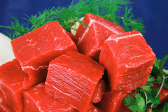 Meat fillet in a white bowls over blue Stock Images
