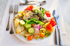 Meat, fish and various vegetable garnish on a plate. Stock Image