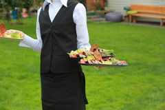 Meat, fish, vegetable canapeson a tray in the hands of the waiter outdoor Stock Image