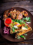 Meat with flat bread,greens and vegetables on ceramic plate. Stock Photography