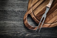 Meat fork chopping board on wood background Royalty Free Stock Photo