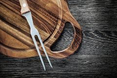 Meat fork cutting board on wood background Royalty Free Stock Photo