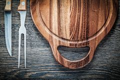 Meat fork knife carving board on vintage wooden background Royalty Free Stock Photos