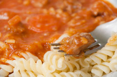 Meat on a fork over goulash with macaroni Royalty Free Stock Photography