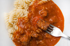 Meat on a fork over goulash with macaroni Royalty Free Stock Photos
