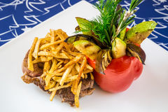 Meat with French fries, vegetables and herbs Stock Photography