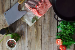 Meat. Fresh and raw meat. Ribs and pork chops on wooden background. Food background include fresh raw ribs and pork chops, pan, olive virgin oil, herbs, mix peas Stock Images