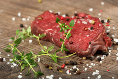 Meat. Fresh raw meat with salt, pepper and herbs on wooden table Stock Photography