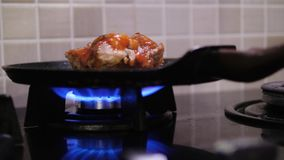 Meat is fried in a pan. Cook fries meat with red sauce in pan in restaurant stock video footage
