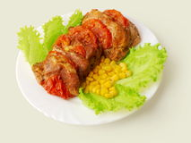 Meat fried in tomatoes decorated... Meat fried in tomatoes decorated with corn and salad placed in the plate over white background Royalty Free Stock Images