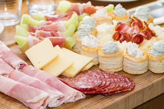 Meat and Fruit Appetizers. An assortment of appetizers made from sliced meats, cheese, melon and biscuits Stock Images