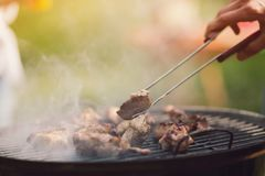 Meat frying on grill outdoors. Chicken meat frying on grill outdoors. Person fliping piece of meat over using kitchen tongs. Smoke coming out of grill royalty free stock photo