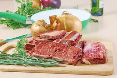 Meat and frying pan. Fresh beef on ribs, on a chopping board, seasonings Stock Photography