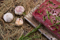 Meat with garlic on the hay. Royalty Free Stock Photos