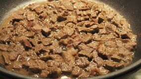 Meat goulash from chicken fillet and onion with spices fry in a pan on the stove. Delicious simple dish close-up.