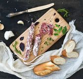 Meat gourmet snack. Salami, garlic, baguette and herbs on rustic wooden board stock photos