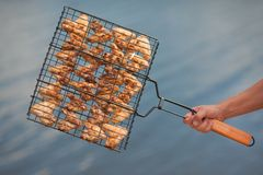 Meat on a grill against water. The hand holds a grill lattice with the prepared meat against water Stock Images