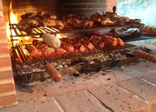 Meat on the grill. Different tipes of meats and sausages stacked on big grill. Italian Cuisine royalty free stock image