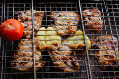 Meat on the grill with vegetables. Pork meat with vegetables is fried on a grate Stock Photos