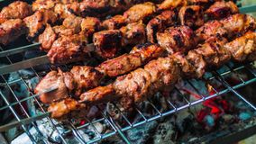Meat grilled on skewers over the glowing. Tasty food for barbecue party. Roasted grill meat with crust. Close up of pork stock footage