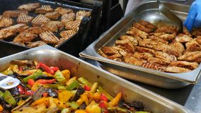 Meat and grilled vegetables cooked and stacked in trays lie on the table in the kitchen of the restaurant, beef, chicken. Meat, turkey meat, pepper, tomatoes stock video