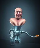 Meat grinder with man inside Royalty Free Stock Photography