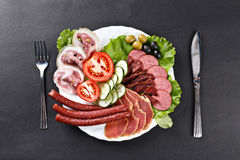 Meat, hamon, sausage slices assortment on plate with spoon and k. Nife Stock Photo
