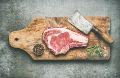 Meat high-protein dinner concept with raw beef steak rib-eye. Flat-lay of raw prime beef meat dry-aged steak rib-eye on bone with seasoning and chopper on wooden Royalty Free Stock Image
