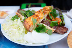 Meat kebab with vegetables on plate Stock Photography