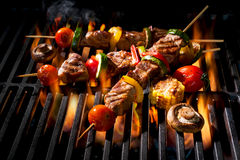 Meat kebabs with vegetables on flaming grill Royalty Free Stock Photo