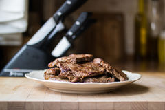 Meat with knife set. Beef with tenderizer on a wooden surfaace Stock Images