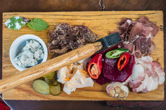 Meat, lard, vegetables on board. Slices fresh pork meat, lard on wooden board with vegetables, spices, stuck ax on the table Stock Photos