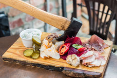 Meat, lard, vegetables on board. Slices fresh pork meat, lard on wooden board with vegetables, spices, stuck ax on the table stock images