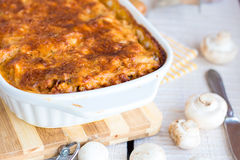 Meat lasagna with mushrooms in a white bowl on a blackboard Stock Photo