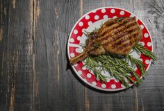 Cooked pork meat with rosemary on dark wooden background Royalty Free Stock Images