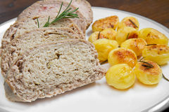 Meat loaf with roasted potatoes on dish Royalty Free Stock Photos