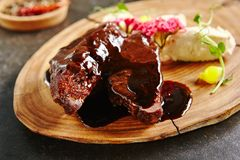Roasted Mutton on Rustic Wooden Background. Meat Main Course with Grilled Lamb Cheeks Poured with Demi Glace Sauce, Cheese and Vegetables. Roasted Mutton on stock image