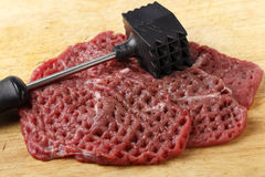 Meat mallet and minute steaks Royalty Free Stock Photography