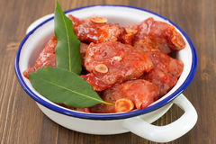 Meat in marinate with garlic and bay leaf. On white dish Royalty Free Stock Images
