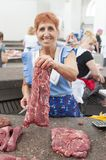 Meat market. Cheerful woman, showing the meat she sells, in the covered meat market of chisinau, located within the central market, Moldova royalty free stock photos