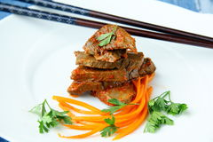 Meat meal. Prepared meat in Chinese on a white plate royalty free stock image