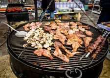 Meat and mushrooms cooking on barbecue at outdoor kitchen Stock Image