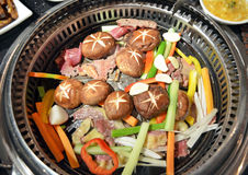 Meat, mushrooms and vegetables cooked in the table embedded barbecue in the restaurant in Ulan Bator Stock Images