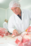 Meat packer cutting meat Stock Photo